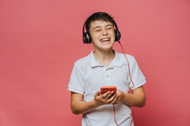 Фото кавказского мальчика в белой футболке любит слушать любимую музыку в наушниках, чувствует себя беззаботным, доволен качеством звука, любит свой плейлист, поет от положительных эмоций