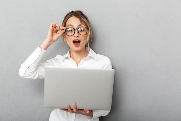 眼鏡をかけて立って、オフィスでラップトップを保持している白人のビジネスライクな女性の写真、分離