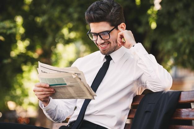 緑豊かな公園のベンチに座って、晴れた日に新聞を読んでスーツを着た白人ビジネスマンの写真