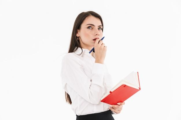 白い壁に隔離されたオフィスで働いている間、フォーマルな服装の手帳を持っている白人女性労働者の実業家の写真