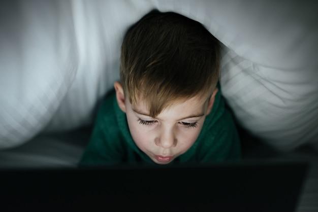 Фотография кавказского счастливого ребенка, скрывающегося под одеялом, играющего на компьютере