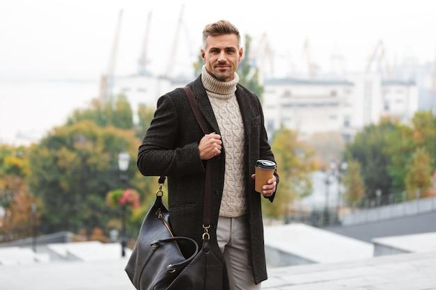 街の通りを歩きながら、持ち帰り用のコーヒーを保持しているジャケットを着ている白人の幸せな男の30代の写真