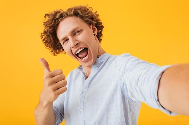 黄色の背景の上に分離された、自撮り写真を撮り、親指を上に表示している白人の喜びに満ちた男の写真