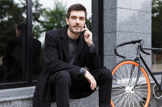 자전거와 함께 야외에 앉아있는 동안 휴대 전화를 사용하는 백인 남자 20 대의 사진