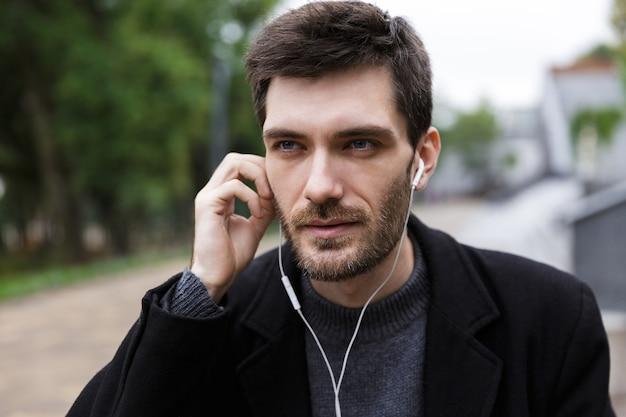 야외를 걷는 동안 휴대 전화를 사용하여 이어폰을 착용 한 백인 남자 20 대의 사진