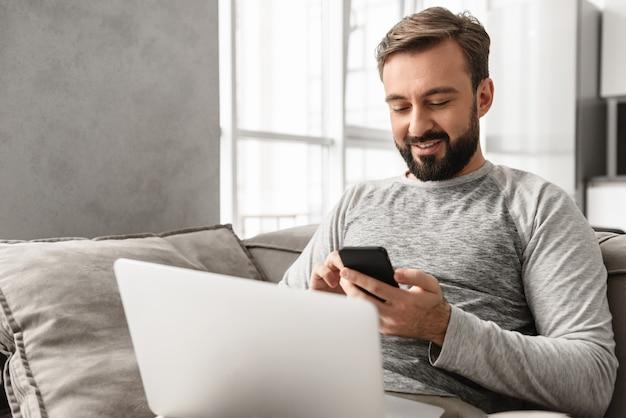 リビングルームでノートパソコンで作業しながら、スマートフォンを使用してカジュアルな服装で30代の白人男性の写真