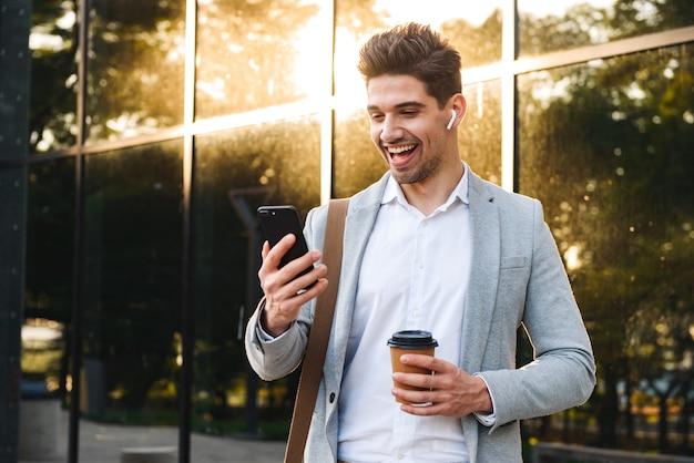 테이크 아웃 커피와 함께 건물 근처에 야외 서있는 동안 휴대 전화를 들고 비즈니스 정장에 백인 남자의 사진