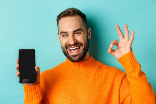 모바일 화면과 괜찮아 기호를 보여주는 백인 남자의 사진, 밝은 파란색 배경 위에 만족 서 온라인 상점, 스마트 폰 앱을 승인합니다.