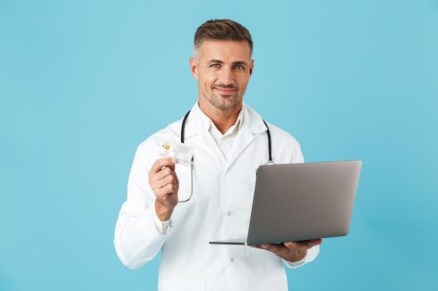 青い壁の上に孤立して立って、ラップトップとクレジットカードを保持している白い医療コートと聴診器を身に着けている白人男性の写真