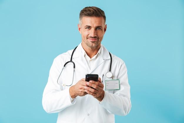 白いコートと聴診器を持ってスマートフォンを保持し、青い壁の上に孤立して立っている白人医師の写真