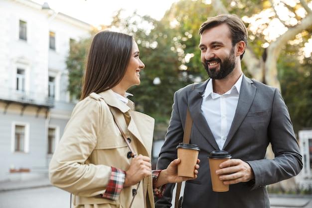 街の通りを歩きながら持ち帰り用のコーヒーを飲むフォーマルウェアの白人サラリーマンの男女の写真