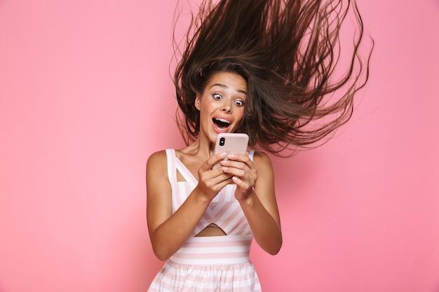 ピンクの壁に隔離された、笑顔で髪を振って携帯電話を保持しているドレスを着ている白人女性20代の写真