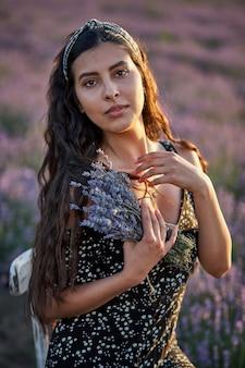 Фото кавказской молодой женщины в платье, держащей букет цветов, на открытом воздухе через лавандовое поле летом