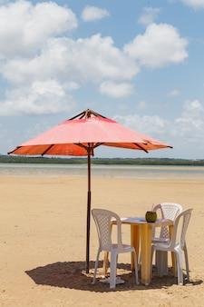 Фотография стульев и зонтика с прудом на заднем плане. пляж, отдых и лето. вертикальный