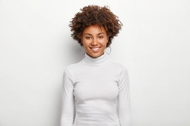 巻き毛のカリスマ的な素敵な女性の写真は、顔に楽しい、歯を見せる笑顔を持っています