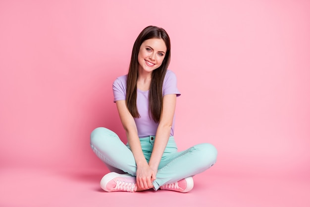 Фотография очаровательной привлекательной девушки сидит на полу, скрестив ноги, наслаждаясь свободным временем, носит фиолетовую одежду, изолированную на розовом цветном фоне