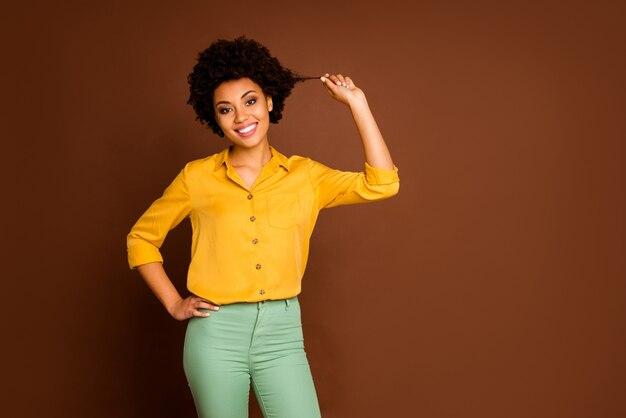 헤어 살롱 마스터를 방문한 후 좋은 결과를 보여주는 물결 모양의 컬을 들고 매력적인 아름다운 어두운 피부 아가씨의 사진은 노란색 셔츠 녹색 바지 절연 갈색 색상을 착용