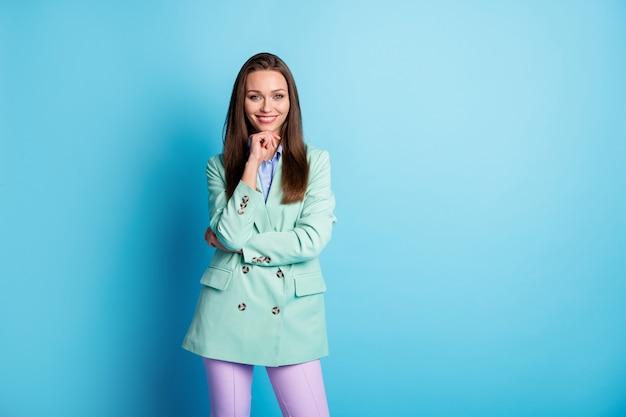 Фото очаровательной бизнес-леди с хорошим настроением, рука на подбородке, тренд, бирюзовый пиджак, брюки, изолированный синий цвет фона