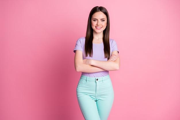 Фото очаровательной бизнес-леди хорошее позитивное настроение руки скрещенные руки самоуверенный властный человек носить повседневную фиолетовую футболку бирюзовые штаны изолированный розовый пастельный цвет фона