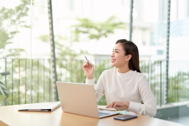 テーブルに座っている魅力的な中国の実業家の写真