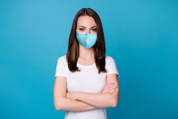 魅力的な自信を持って女性の腕の手が交差した偉そうな労働者インテリジェントな人成功したキャリアチームメンバーの写真カジュアルな医療マスク白いtシャツ孤立した青い色の背景を着用してください