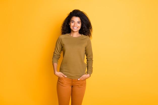 생생한 컬러 배경 위에 절연 주황색 바지를 입고 주머니에 손을 잡고 매력적인 귀여운 쾌활한 좋은 여자 친구의 사진