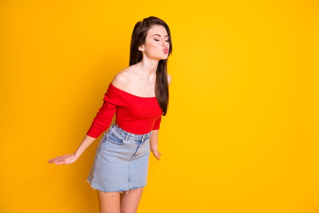 매력적인 귀여운 소녀의 젊은 여성 입술의 사진은 공기 키스 남자 친구 사랑 닫힌 눈 셔츠를 덮은 어깨 데님 미니 스커트 고립 된 밝은 노란색 배경을 보냅니다