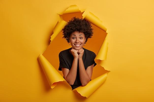 매력적인 귀여운 젊은 아프리카 계 미국인 여자의 사진은 카메라에 즐겁게 미소 짓고, 턱 아래에 양손을 유지하고, 검은 옷을 입은 하얀 치아를 보여줍니다.