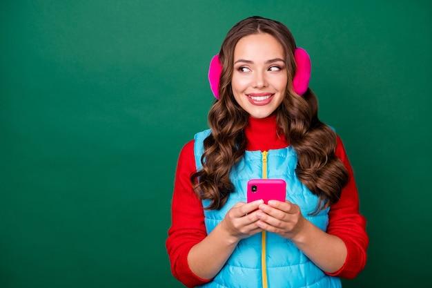 魅力的なかわいい若い女性の外観の写真コピースペースは電話を共有します良い興味深いニュースソーシャルメディアはピンクのイヤウォーマーを着用します青いジップベスト赤いプルオーバー孤立した緑色の背景