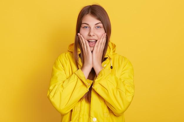 Фотография очаровательной возбужденной молодой женщины с длинными волосами, с открытым ртом, в желтой куртке, изолированной на желтом