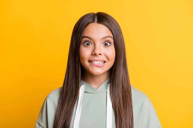 Фотография очаровательной смешной детской девочки, одетой в повседневный зеленый наряд, кусающая губу, изолировала желтый цвет фона