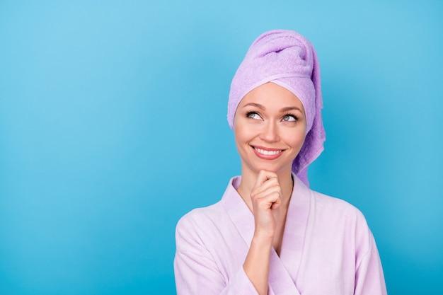 매력적인 여자 팔 턱의 사진은 빈 공간 빛나는 미소를 입고 보라색 수건 터번 목욕 가운 격리 된 파란색 배경을 찾습니다