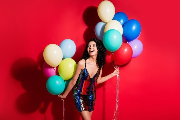 Фотография очаровательной девушки держит много воздушных шаров, выглядит пустое пространство, носит глянцевое короткое платье, изолированное ярким красным цветом фона