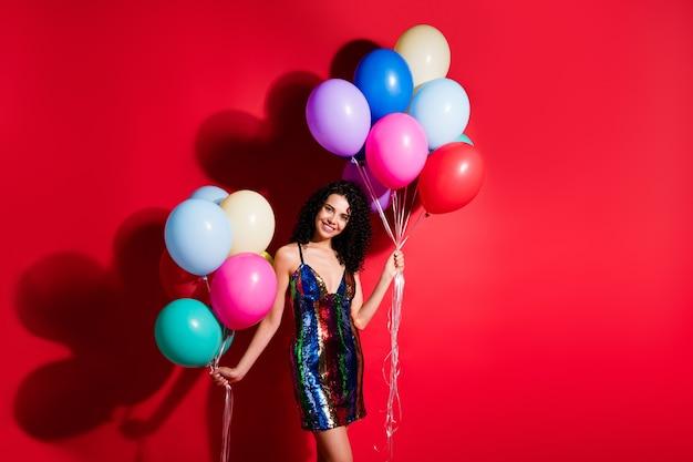 Фотография очаровательной девушки держит много воздушных шаров, блестящая сияющая улыбка, одетая в глянцевое короткое платье, изолирована ярким красным цветом фона