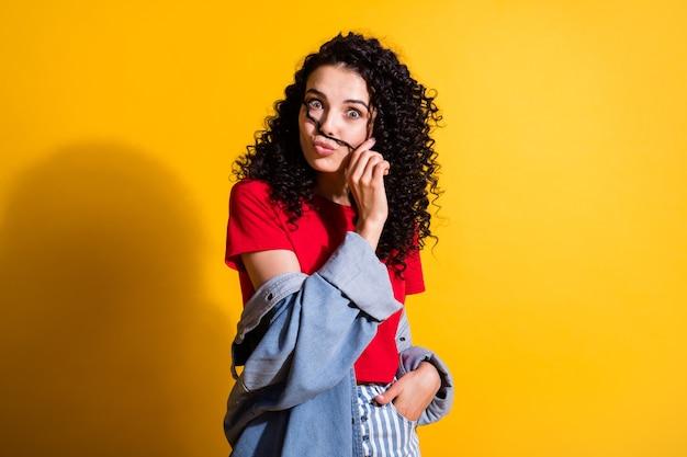 魅力的な女の子の写真は、カールホールドムスタチオの口唇が赤いトップストライプのジーンズジャケットを着用し、黄色の背景を分離しました