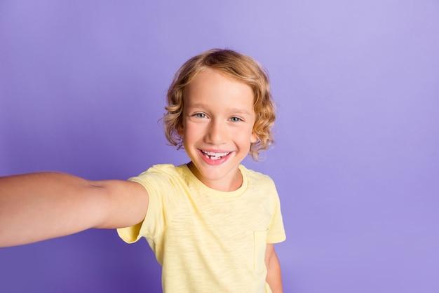 魅力的な子供の男の子の写真は、紫色の背景の上に分離されたカジュアルなスタイルの服を自画像に着用させます