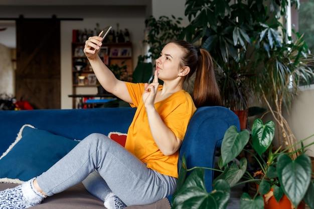 魅力的な女性が電話を持って自分撮りをしている写真スカイプを振って手のひらを振ってこんにちは座っている快適なソファは屋内でカジュアルな黄色のシャツのアパートを着て、周りの観葉植物