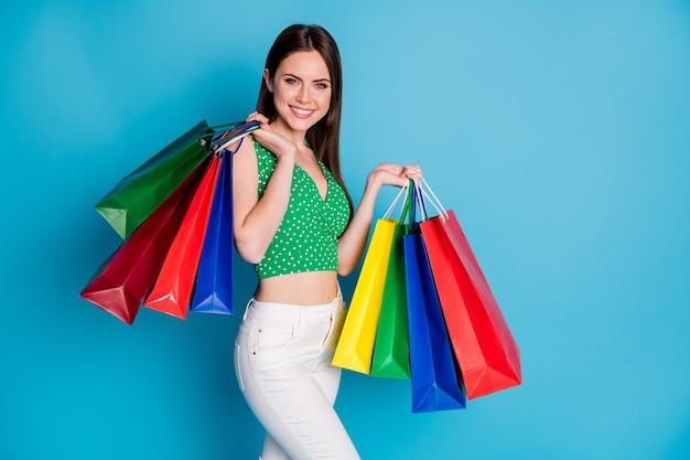 魅力的な素敵な女の子の写真は買い物を楽しむ多くのバッグは青い色の背景の上に分離された白いズボンズボン一重項を着用します