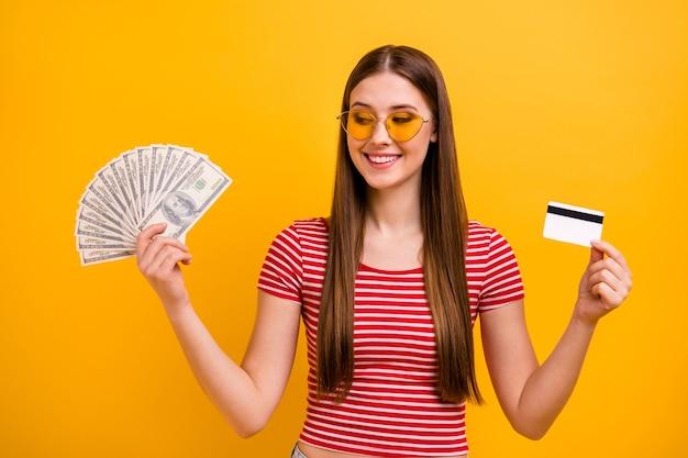 魅力的な素敵な女の子らしい若い女の子の写真は、宝くじの大当たりが太陽のスペックを着用する方法を夢見ているクレジットカードドルの現金ファンを保持していますストライプの白赤シャツ鮮やかな黄色の背景