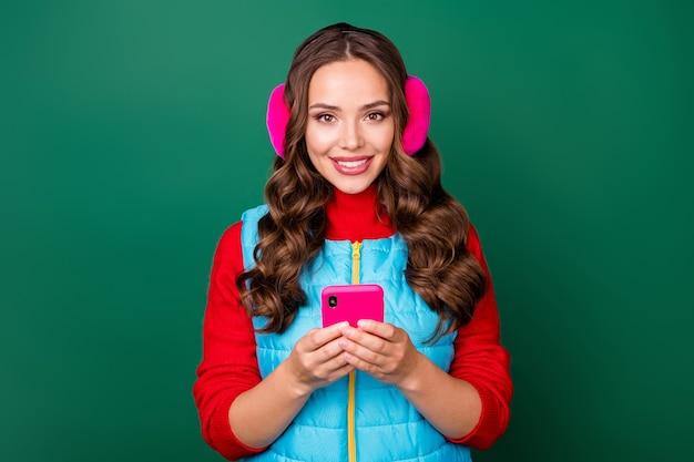 魅力的な素敵な若い女性の写真は電話チャットのボーイフレンドを保持します一般的な写真を共有しますソーシャルネットワークはピンクのイヤウォーマーを着用します青いベスト赤いプルオーバー孤立した緑の色の背景