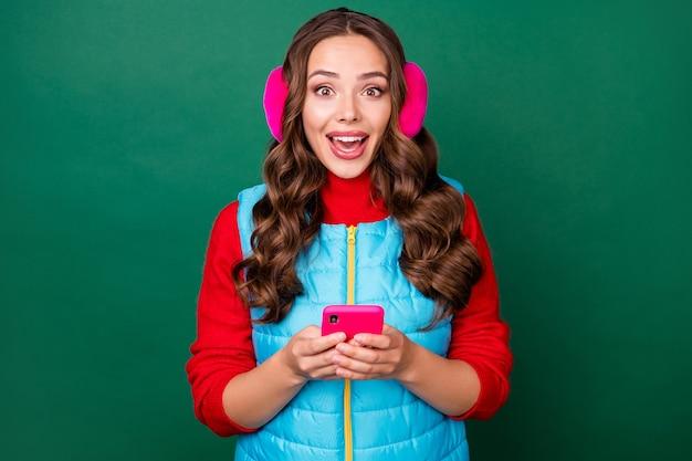 魅力的なかわいい若い女性の写真興奮した口を開けて電話をかける素晴らしいニュースを読むカフェオープニングウェアピンクのイヤーウォーマーブルーのジッパー付きベスト赤いプルオーバー孤立した緑色の背景