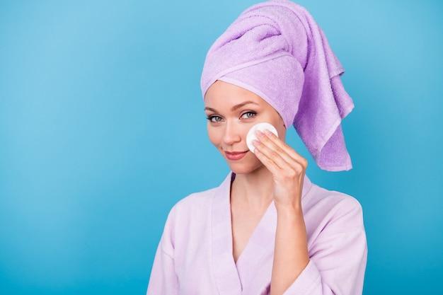 매력적인 여성의 손이 흰색 스폰지 광대뼈를 잡고 보라색 수건 터번 목욕 가운을 입은 사진은 파란색 배경에 격리되어 있습니다.