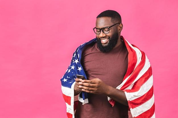 Фото веселого американского афроамериканца, протестующего поднять американский национальный флаг, чернокожие люди, революция, любовь, все люди, выражают единство, солидарность, изолированные на розовом фоне. с помощью мобильного телефона.