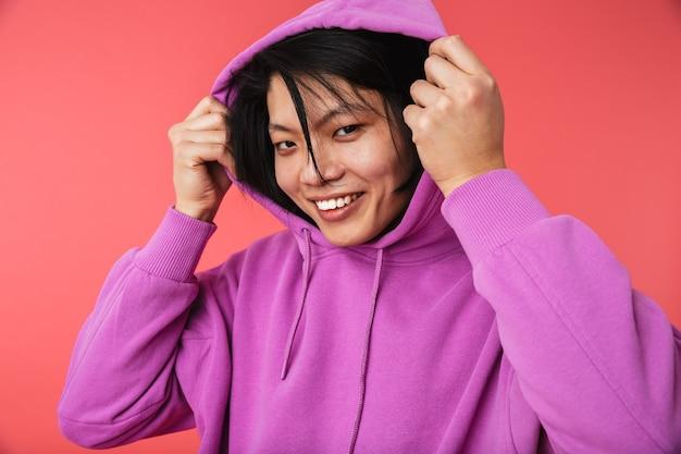 Фотография веселого азиатского парня в толстовке, радующегося и улыбающегося в камеру, изолированную над красной стеной
