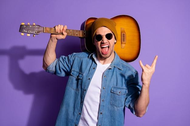 Фотография веселого привлекательного рокера, кричащего модно, показывает вам, рок-знак, пальцы рогатые, держа акустическую гитару в плече в джинсовых очках, изолированный фиолетовый яркий цветной фон