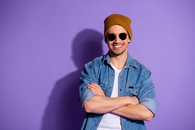 쾌활한 매력적인 이빨 프리랜서의 사진은 보라색 생생한 컬러 배경 위에 절연 안경을 착용 접혀 팔로 자신있게 서