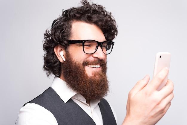 스마트 폰 및 earpods를 사용하여 쾌활한 수염 비즈니스 남자의 사진