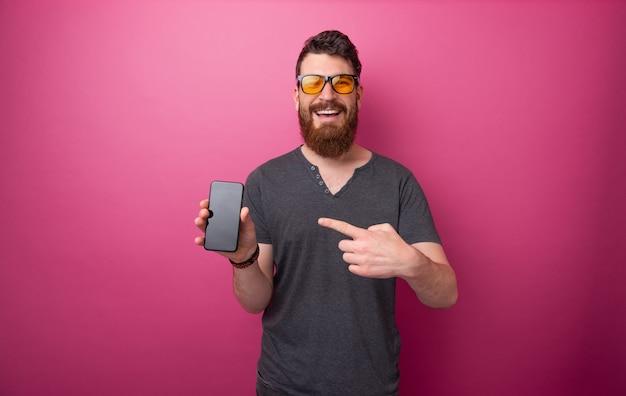 スマートフォンを指してピンクの背景の上に立っている陽気なひげを生やした男の写真