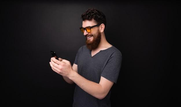 スマートフォンを使用してsmsテキストを入力する陽気なひげを生やした男の写真
