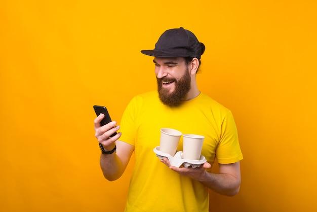 行くために2杯のコーヒーを保持し、電話を使用して黄色のtシャツで陽気なひげを生やしたヒップスターの男の写真